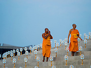 """11 FEBRUARY 2016 - KHLONG LUANG, PATHUM THANI, THAILAND: Buddhist monks walk to their seat during the Makha Bucha Day service at Wat Phra Dhammakaya.  Makha Bucha Day is a public holiday in Cambodia, Laos, Myanmar and Thailand. Many people go to the temple to perform merit-making activities on Makha Bucha Day, which marks four important events in Buddhism: 1,250 disciples came to see the Buddha without being summoned, all of them were Arhantas, or Enlightened Ones, and all were ordained by the Buddha himself. The Buddha gave those Arhantas the principles of Buddhism. In Thailand, this teaching has been dubbed the """"Heart of Buddhism."""" Wat Phra Dhammakaya is the center of the Dhammakaya Movement, a Buddhist sect founded in the 1970s and led by Phra Dhammachayo. Makha Bucha Day is one of the most important holy days on the Thai Buddhist calender.      PHOTO BY JACK KURTZ"""