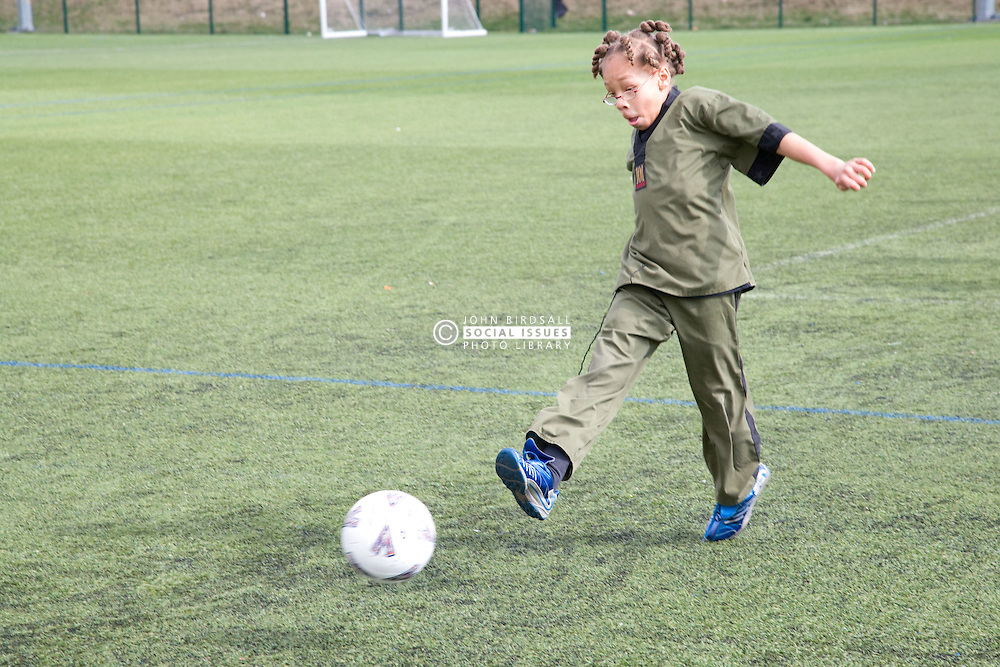 Young boy kicking a football on a playing field at his local leisure centre,