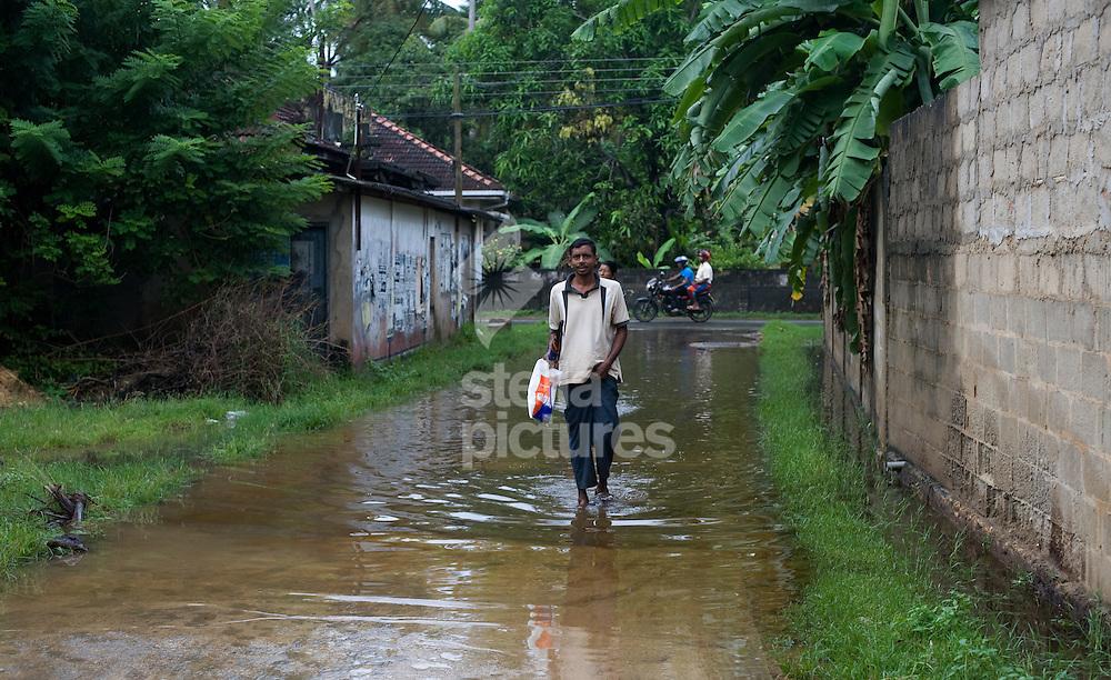 Picture by Daniel Hambury. .10/12/10..A local man wades through flood water in Marissa, Sri Lanka.
