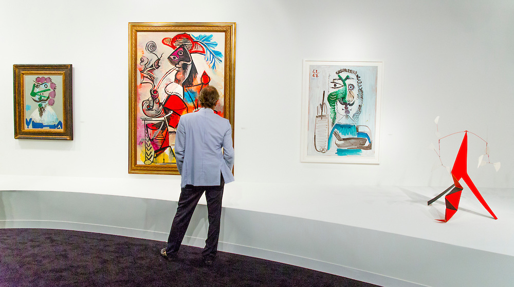 Man studies a Picasso painting plus at far right  an Alexander Calder mobile at Art Basel Miami Beach 2015