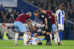 Brighton & Hove Albion's Beram Kayal lies injured on the pitch after being fouled by West Ham United's Marko Arnautovic (left)