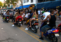 A group of people passing by on motorcycle on Ocean Drive on the Miami Beach Urban Weekend 2008.The Miami Beach Urban weekend in the largest Urban Festival in the World, that caters toward the Hip Hop Generation. Over 300.000 participants make the annual trek to South Beach for 4 days full of fun, food, festivities, entertainment, music, and more.