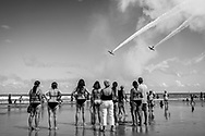 Daytona Beach, FL, USA - October 12, 2014: People on Daytona Beach look up at GEICO Skytypers flying the SNJ-2 aircraft, manufactured in the 1940s. The planes were part of the 2014 Wings and Waves Air Show in Daytona Beach, Florida.