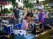 """30 MARCH 2013 - BANGKOK, THAILAND:  A woman works at her sewing stand on Sukhumvit Road in Bangkok while a tourist walks by her. Thailand's economic expansion since the 1970 has dramatically reduced both the amount of poverty and the severity of poverty in Thailand. At the same time, the gap between the very rich in Thailand and the very poor has grown so that income disparity is greater now than it was in 1970. Thailand scores .42 on the """"Ginni Index"""" which measures income disparity on a scale of 0 (perfect income equality) to 1 (absolute inequality in which one person owns everything). Sweden has the best Ginni score (.23), Thailand's score is slightly better than the US score of .45.  PHOTO BY JACK KURTZ"""