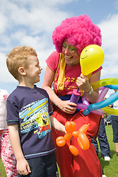 Clown at a Parklife summer activities event showing balloon modelling to a young boy,
