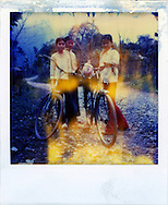 Portrait of young vietnamese girls going to school with their bicycle. Northern Vietnam, Asia. The polaroid is really updated and present yellow trace on its surface.