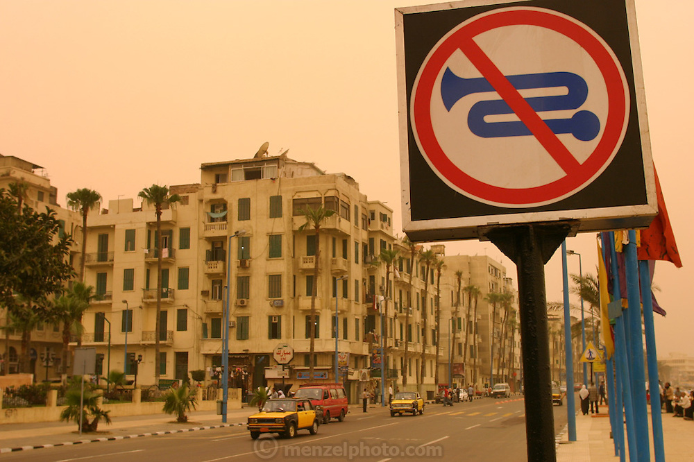 A 'no-honking' sign in downtown Alexandria, Egypt during a sandstorm. The yellow-orange light is from the sand in the sky filtering the sunlight.