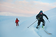 Michelle Blade (left) and Kiya Riverman ski down Hallwylfjellet, Svalbard at sunset.