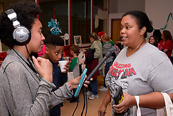 Betzaida Dunn is interviewed by WHYY's Taylor Allen during the winter fest celebration at the Free Library branch in Olney, on December 16, 2018. (Bastiaan Slabbers for WHYY)