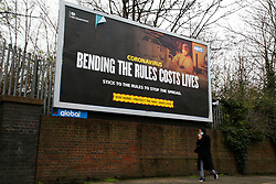 © Licensed to London News Pictures. 01/02/2021. London, UK. A woman wearing a protective face covering walks underneath the government's 'Bending the rules costs lives' awareness publicity campaign poster in north London. Covid-19 infection rates are continuing to drop across London. According to a Government scientific adviser, the UK could be easing out of restrictions in March and back to almost normal by summer if vaccines are 70 to 80 per cent effective at blocking transmission. Photo credit: Dinendra Haria/LNP