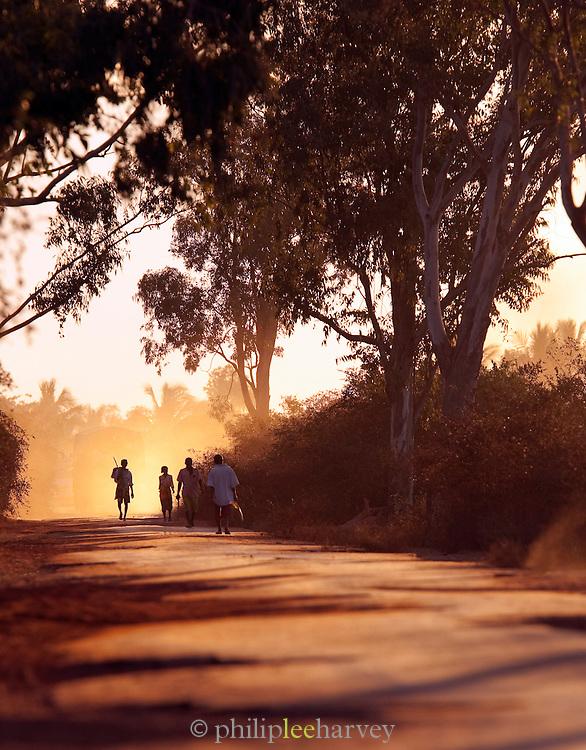 People walk along the dusty road that goes towards Morondava, Madagascar