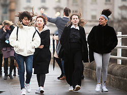 © Licensed to London News Pictures. 14/01/2020. London, UK. Members of the public brave the windy conditions as they cross Waterloo Bridge as storm Brendan hits the capital. Photo credit: Joshua Bratt/LNP