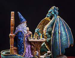 An epic game of chess between a wizard and a dragon in this fantasy scene.