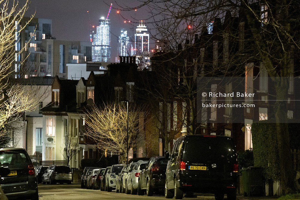 The glow of distant buildings overlooks parked cars and homes in a dark residential street in Herne Hill, south London on 21st January 2021, in London, England.