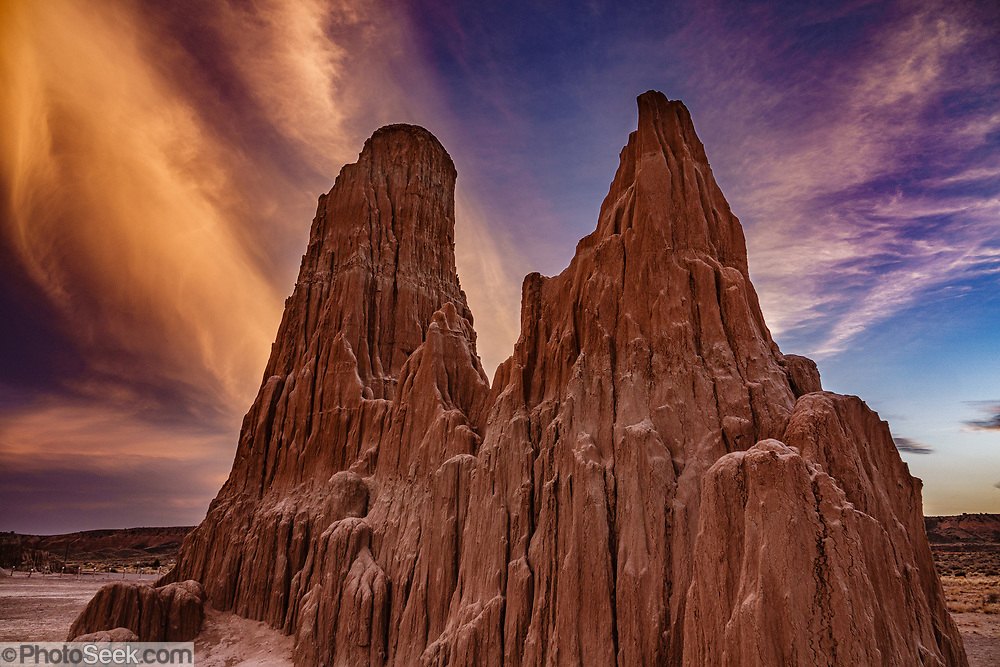 Sunset colors clouds above mud towers in Cathedral Gorge State Park, Panaca, Nevada, USA. Million-year-old lake sediments have eroded into fantastic mud castles at Cathedral Gorge State Park.