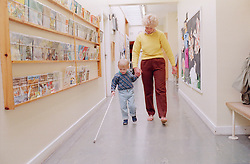 Young child with visual impairment walking along school corridor using walking cane and holding carer's hand,