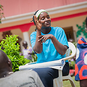 CAPTION: SignHealth Uganda often uses its volunteers to put on short dramas at events in order to heighten awareness and challenge the stigmas attached to hearing impairment. In this scene, one of the volunteers is teaching a family how to communicate using sign language.  LOCATION: Kakunyu Inclusive Nursery and Primary School, Kakunyu Village, near Masaka city, Lweongo District, Central Region, Uganda. INDIVIDUAL(S) PHOTOGRAPHED: Elizabeth Nakiberu.