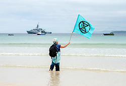 © Licensed to London News Pictures; 11/06/2021; St Ives, Cornwall UK. G7 summit in Cornwall. A woman waves an XR flag with HMS Tamar in the background at a protest by Extinction Rebellion in St Ives on the first day of the G7 summit. Photo credit: Simon Chapman/LNP.