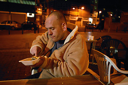 Man eating a meal from a mobile soup kitchen in Nottingham,