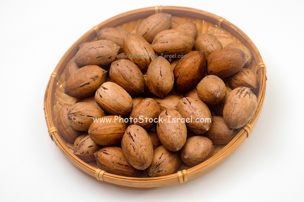 Whole Pecan Nuts in a straw dish on white background
