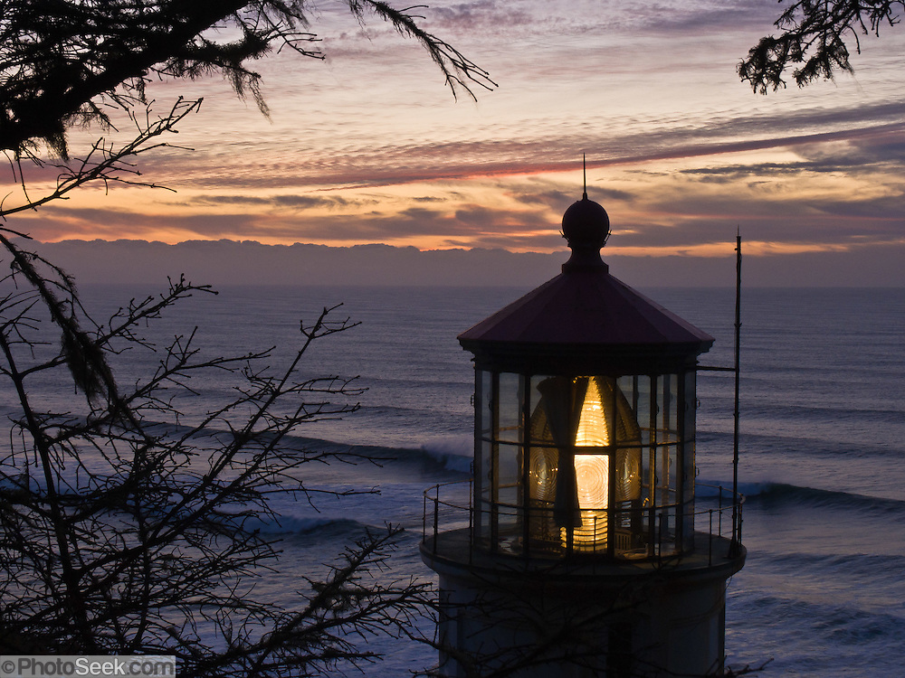 Heceta Head Lighthouse at sunset in winter, at Heceta Head Lighthouse State Scenic Viewpoint, on the Oregon coast, USA. Here, the Siuslaw Indians traditionally hunted sea lions and gathered sea bird eggs from offshore rocks. While seeking to extend Spanish hegemony in the late 1700s, Spanish explorer Bruno de Heceta mapped the mouth of the Columbia River and much more along the Pacific Northwest coast; and in 1862, the US Coast Survey named Heceta Head in his honor. Built atop a 56-foot tower in 1893, this Lightstation's coastal safety beacon was first illuminated in 1894. Perched 205 feet above the ocean, its fresnel lens focuses the brightest light on the Oregon coast, visible up to 21 miles out to sea. Heceta Head is found halfway between Yachats and Florence (2.1 miles south of Carl Washburne State Park). From the large parking lot, walk 1 mile round trip to the Lighthouse. (Heceta Head Lighthouse State Scenic Viewpoint was created in the 1990s by combining Heceta Head State Park with the former Devils Elbow State Park at the scenic cove at the mouth of Cape Creek.)