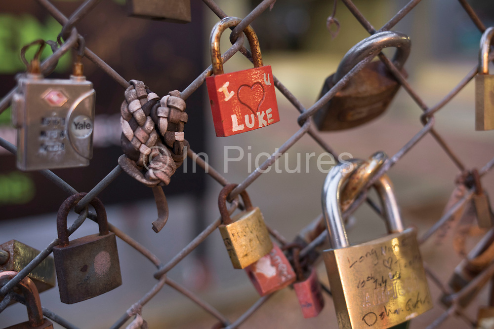 Lovers padlocks attached to a fence in Shoreditch in London, United Kingdom. Love padlocks, also known as love locks and, in Taiwan, wish locks, are a custom by which padlocks are affixed to a fence, gate, bridge or similar public fixture by sweethearts at an increasing number of locations in the world by couples and friends to symbolize their love.