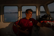 Vinalhaven, ME 7/29/19 6:48:29 PM <br /> Richie Carlsen, 54, of Vinalhaven, a lobsterboat captain and volunteer EMT, on his lobsterboat on Vinalhaven, Maine, on Monday, July 29, 2019. Carlsen volunteers his captain services and his boat to take people who need a hospital to the mainland during times when the ferry isn't running and Lifeflight isn't available. The island of Vinalhaven is a popular summer vacation destination whose winter population is 1,200. It lies 14 miles off the coast of Maine.<br /> <br /> Sarah Rice for AARP