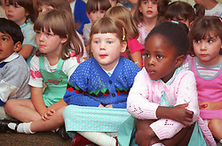 Multiracial group of nursery school pupils sitting on floor in infant school assembly,
