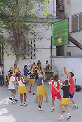 Group of children playing basketball in school playground,