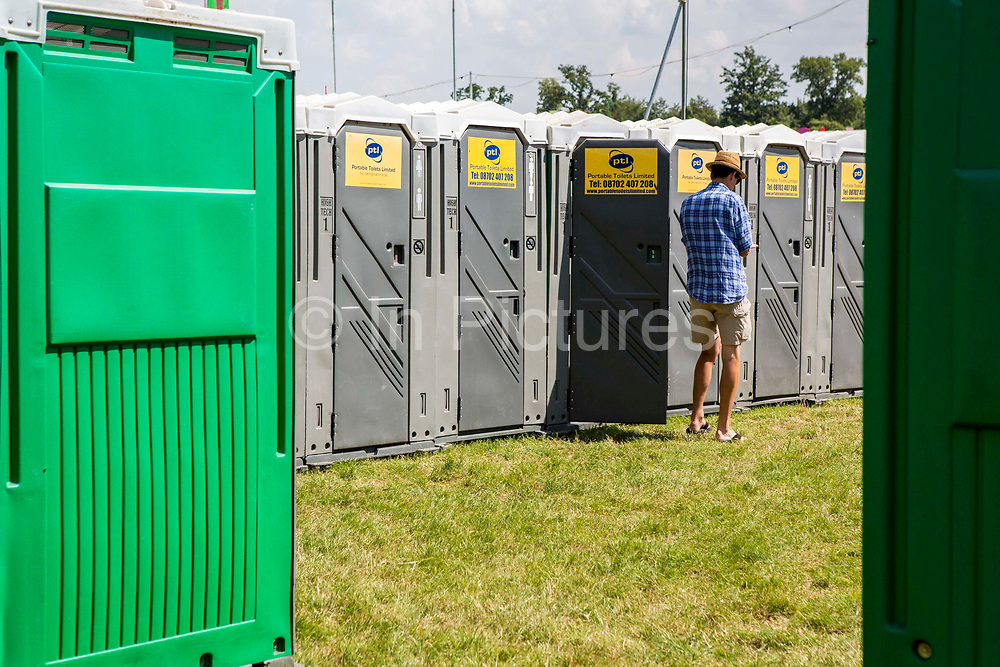 A man exits a portable toilet.  WOMAD 2014, festival of world music and dance, Charlton Park, Wiltshire. UK.