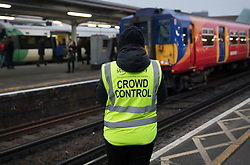 © Licensed to London News Pictures. 19/12/2016. London, UK. A worker wearing a Crowd Control bib watches over a platform at Clapham Junction. Some Southern Rail services are running today as ASLEF union drivers started a two day strike in a dispute over driver-only operated trains. Photo credit: Peter Macdiarmid/LNP