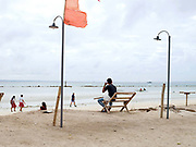 Beach scene in Santa Fe, Bantayan Island, The Philippines. A man sitting on a wooden bench watches while school girls walk along the beach and fishermen prepare their nets to go out to sea.