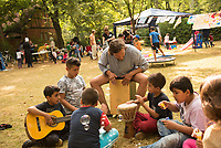 DEU, Deutschland, Germany, Berlin, 19.08.2015: Der Musiker Jan Weigel (M), Freiwilliger Helfer der Initiative Moabit Hilft, macht zusammen mit Flüchtlingskindern Musik auf dem Gelände des Landesamts für Gesundheit und Soziales (LaGeSo), hier befindet sich die Zentrale Aufnahmeeinrichtung des Landes Berlin für Asylbewerber.