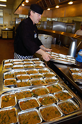 Chef prepares vegetable curry for hospital menu in NHS hospital kitchen West Yorkshire UK