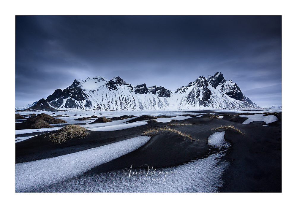 A windswept beach with volcanic black sand dunes and covered with a dusting of snow under a moody sky
