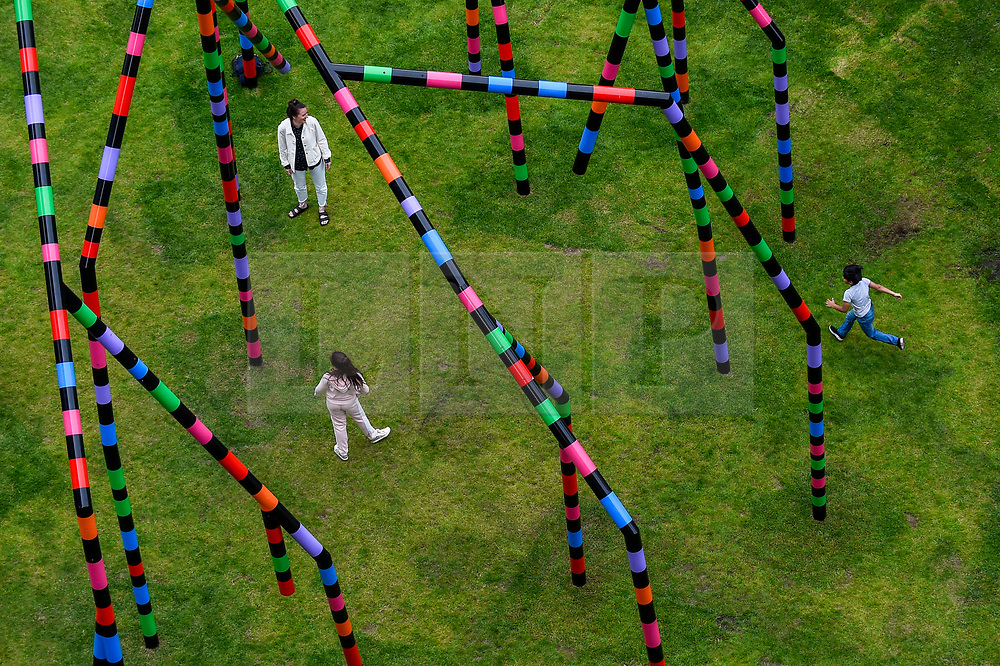 "© Licensed to London News Pictures. 16/07/2020. LONDON, UK.  Children playing at the unveiling of ""My World and Your World"", by major contemporary London-based, Irish artist Eva Rothschild.  The new 16m high public sculpture in Lewis Cubitt Park in King's Cross resembles a lightning bolt, painted in black, purple, pink, orange, green and red stripes.  The coronavirus lockdown caused the April 2020 launch to be postponed, but the unveiling has been able to go ahead now that certain lockdown restrictions have been eased by the UK government.  Photo credit: Stephen Chung/LNP"