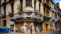 Central figure at a street corner with a deteriorated building behind, in Havana Centro.