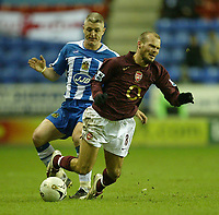 Photo: Aidan Ellis.<br /> Wigan Athletic v Arsenal. Carling Cup. Semi Final, 1st Leg.<br /> 10/01/2006.<br /> Wigan's Graham Kavanagh clips Arsenal's Freddie Ljunberg