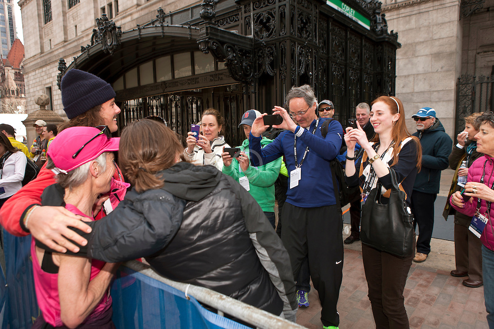 2013 Boston Marathon: Joan Benoit Samuelson poses for husband Scott taking picture with with son Anders, daughter Abby after finishing
