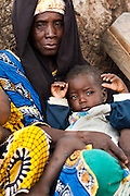 A child sits on her mother's lap as they wait for vaccination in the village of Banankoro, Mali on Saturday August 28, 2010.