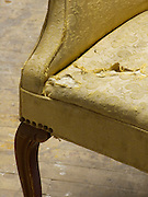 close up of the worn fabric of an old arm chair