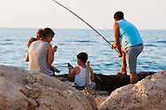 Beirut, Lebanon - September 18, 2010: A family together on the Beirut corniche in the early evening. The husband is fishing, the wife is holding a child and lighting a cigarette, and a second child is holding a mobile phone.