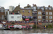 Putney. London.  2004 University Boat Race,  Championships Course, Putney to Mortlake. <br /> Spectators watch the  Oxford and Cambridge, boat race  at Furnival BC and surrounding houses  Hammersmith .  <br /> <br /> [Mandatory Credit Peter SPURRIER]