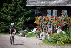 Mountain biker riding on road by a typical black forest house