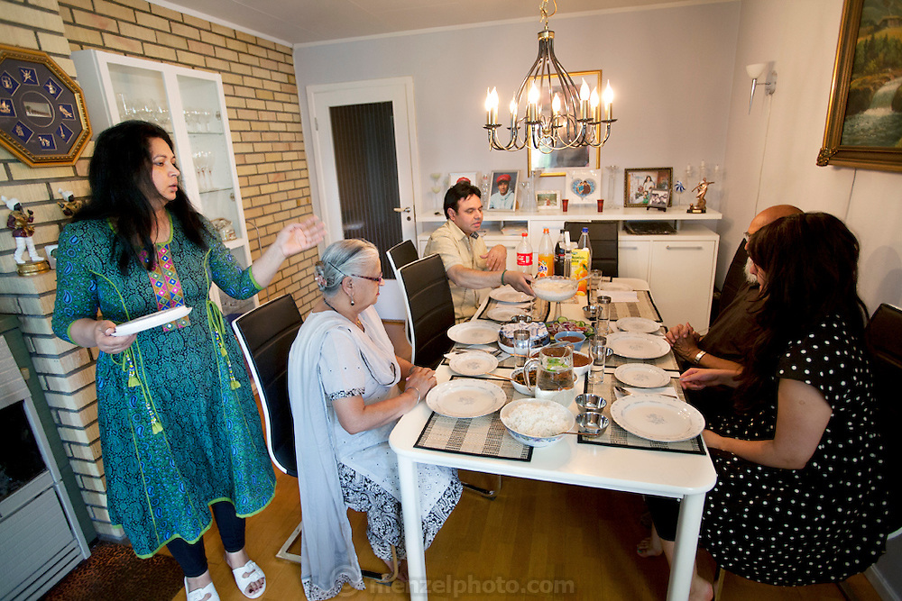 The Qureshi family of Lorenskog, Norway, an Oslo suburb. Pritpal Qureshi, 49, her husband Nasrullah, and their daughter Nabeela, 23 with Pritpal's parents, the Sakhi's, at a weekend lunch in their home. Model-Released.