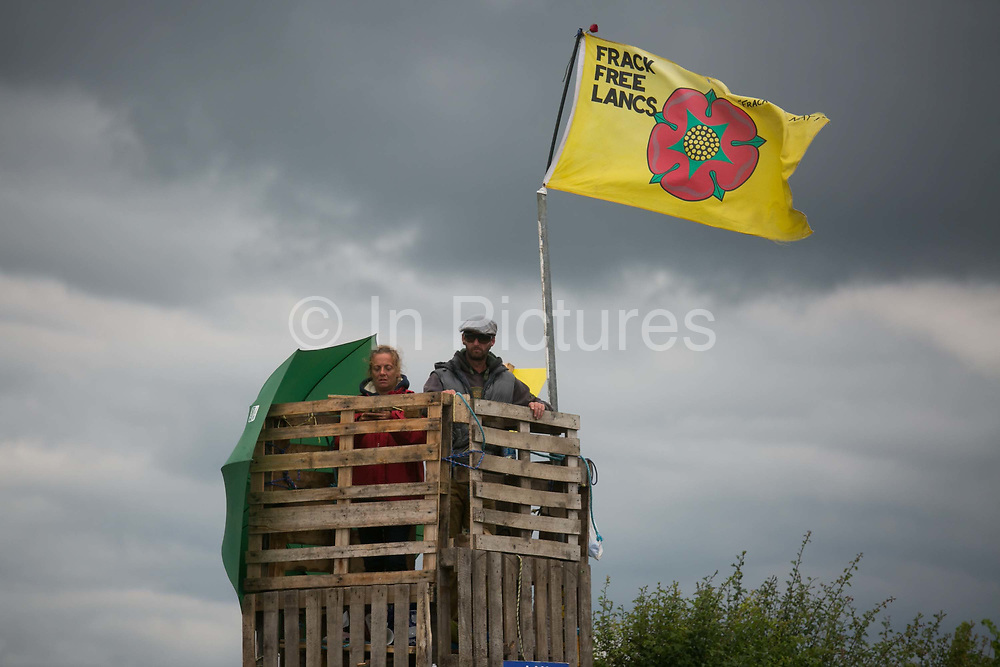 Anti-fracking  activists and protesters outside the gates of Quadrillas fracking site June 31st, New Preston Road, Lancashire, United Kingdom. Two activists up a tower made of pallets build over night. The struggle against fracking in Lancashire has been going on for years. The fracking company Quadrilla is finally ready to bring in a drill tower to start drilling and anti-frackinhg activists are waiting in front of the gates to block the equipment getting in. Fracking is a destructive and potential dangerous and highly contentious method of extracting gas and this site will be the first of many in the United Kingdom reaching miles out under ground.