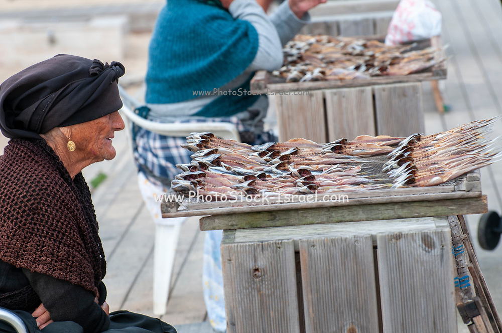 Fishmonger sells sun dried fish on the beach at Nazare, Portugal