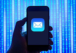 Person holding smart phone with Apple Mail logo displayed on the screen. EDITORIAL USE ONLY