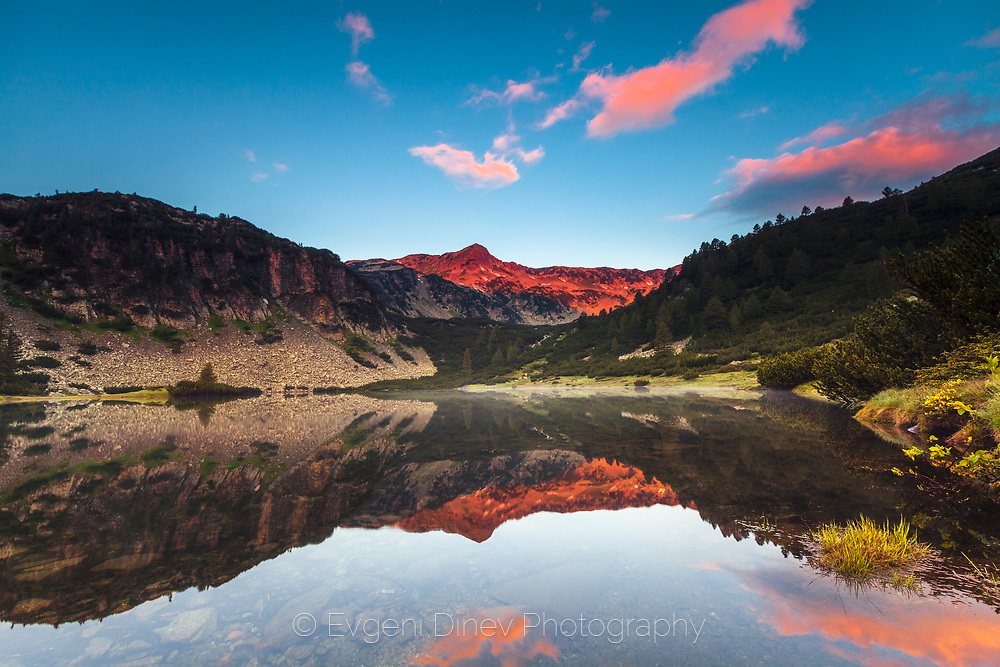 Reflections of a mountain ridge in a lake at sunrise