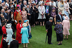 Queen Elizabeth II and the Duke of Edinburgh (both right) greet guests at a garden party at Buckingham Palace in London.
